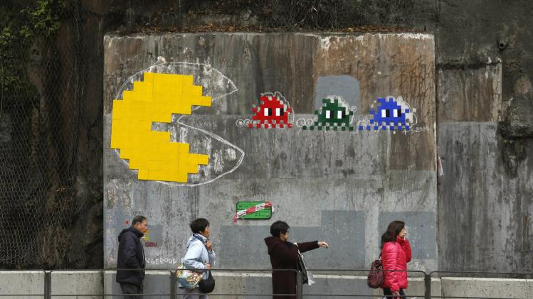 "People walk past a copy of an Pac-Man art piece by French urban artist ""Space Invader"", in Hong Kong"