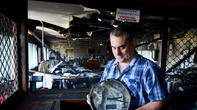 Wasleys Bowling Club Secretary Brad McDougall holds a clock that stopped at the time a bushfire destroyed the clubhouse in the town of Wasleys, located north of Adelaide, South Australia