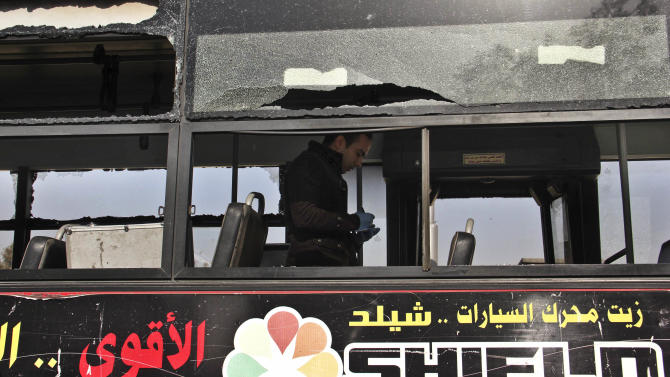 An Egyptian inspector takes notes after an explosion hit a public bus, in Cairo's eastern Nasr City district, Egypt, Thursday, Dec. 26, 2013. Security officials say the explosion wounded several people. The officials say the blast went off Thursday morning. (AP Photo/Mohammed Abu Zaid)