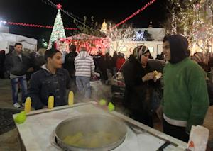 A man sells corn on the cob in Manger Square as people …