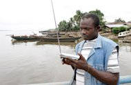 A a man listens to the radio on August 14, 2008 at Ikang River, in Cross River State, Nigeria. Only two survivors have been found so far after a boat capsized off Nigeria with an estimated 128 people on board, emergency officials said on Wednesday