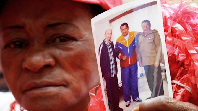 """A supporter of Venezuela's President Hugo Chavez holds a photo of him, alongside Cuba's Raul Castro, right, and Fidel Castro, during a event to commemorate the violent street protests of 1989 known as the """"Caracazo,"""" in Caracas, Venezuela, Wednesday, Feb. 27, 2013. The wave of 1989 violent protests, seen by the current government as a """"popular uprising,"""" was in response to the economic measures imposed by then President Carlos Andres Perez. (AP Photo/Fernando Llano)"""