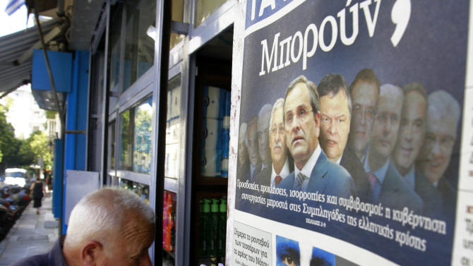 A man enters a kiosk that sells newspapers as the newspaper on the right shows the new Greek government, in Athens, Friday, June 22, 2012. Greek authorities say the country's new prime minister, Antonis Samaras, will undergo eye surgery this weekend for a detached retina discovered during a routine examination.(AP Photo/Petros Karadjias)