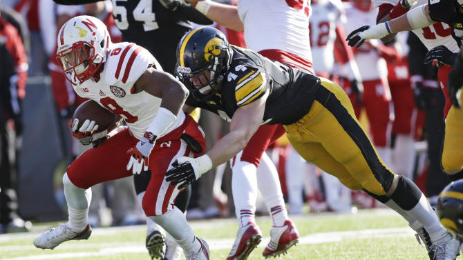 Nebraska running back Ameer Abdullah tries to break a tackle by Iowa linebacker James Morris, right, during the first half of an NCAA college football game, Friday, Nov. 23, 2012, in Iowa City, Iowa. (AP Photo/Charlie Neibergall)