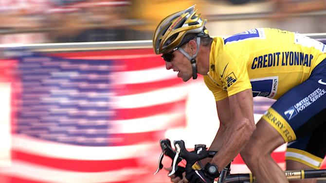 FILE - In this July 25, 2004 file photo, overall leader Lance Armstrong, of Austin, Texas, rides down the Champs Elysees avenue past U.S. flags during the 20th and last stage of the Tour de France cycling race between Montereau, southeast of Paris, and the Champs-Elysees in Paris. Federal prosecutors said, Friday, Feb. 3, 2012, they are closing a criminal investigation of Armstrong and will not charge him over allegations the seven-time Tour de France winner used performance-enhancing drugs. (AP Photo/Franck Prevel, File)