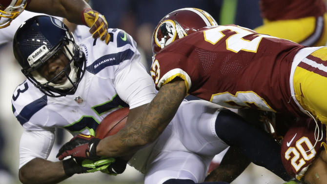 Seattle Seahawks running back Leon Washington is stopped by Washington Redskins cornerback DeAngelo Hall during the first half of an NFL wild card playoff football game in Landover, Md., Sunday, Jan. 6, 2013. (AP Photo/Evan Vucci)