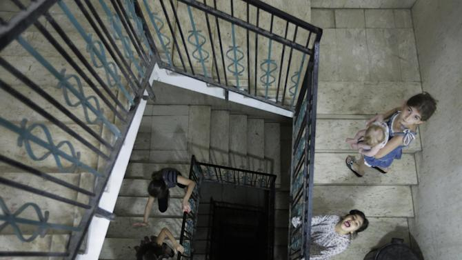 Restricted from playing outside, displaced Palestinian children play indoors in a high-rise building where their families had rented flats for them to live, after leaving their homes due to the unrest, in Gaza City, Sunday, Aug. 10, 2014. (AP Photo/Lefteris Pitarakis)