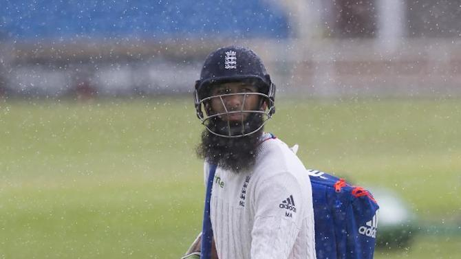 England's Moeen Ali makes his way back to the pavilion during a rain shower at nets the day before the second Test match between England and New Zealand at Headingley cricket ground in Leeds, England, Thursday, May 28, 2015.(AP Photo/Jon Super)