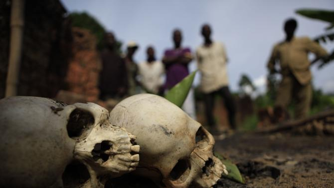 In this May, 23, 2011 photo, men look at the skulls of young brothers who witnesses said were killed in March by being locked inside a house that was then set on fire by Republican Forces soldiers allied with President Alassane Ouattara, in the village of Bably Vaya, near Blolequin, western Ivory Coast. Ouattara has pledged to investigate the killings of thousands of people during the war on both sides. Even after the war, however, Ouattara's forces have killed at least 500 people, according to human rights groups. And he seems powerless to stop them, or even acknowledge what they are doing. (AP Photo/Rebecca Blackwell)