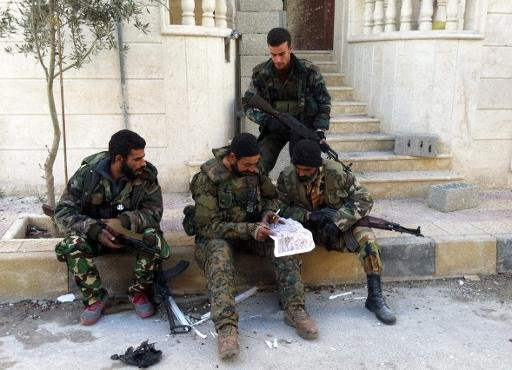 Syrian pro-government forces read a map in the town of Nabak near Damascus on December 7, 2013