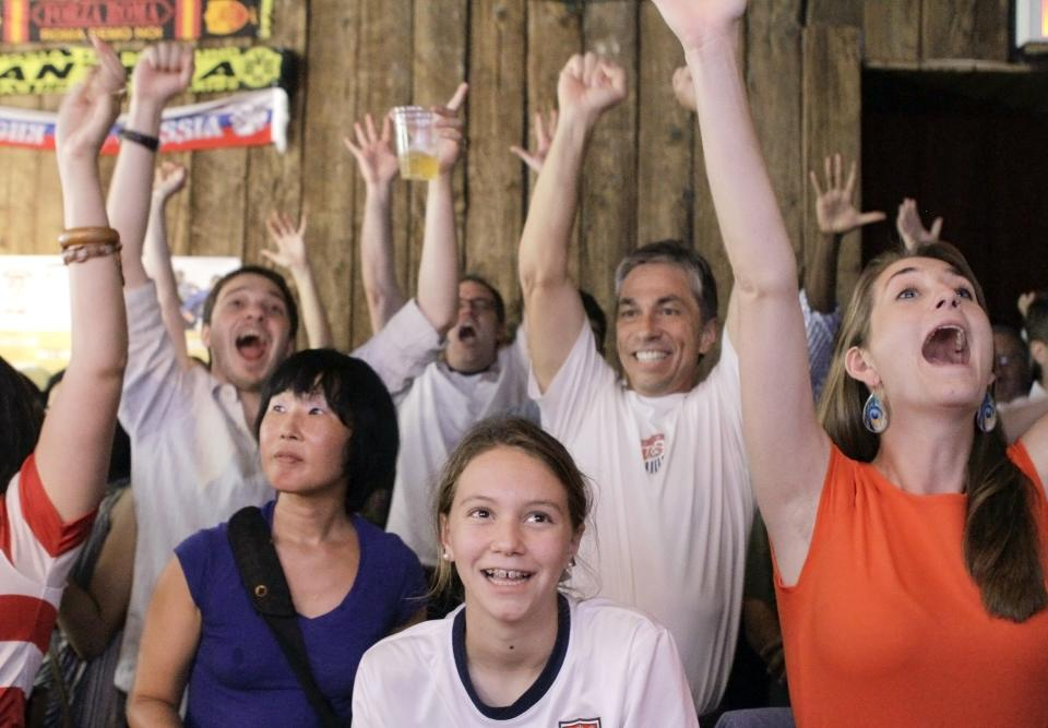 People react as they watch a television broadcast of the United States women's soccer team taking on Japan in the gold medal match at the 2012 London Summer Olympics, Thursday, Aug. 9, 2012, at Nevada Smiths bar in New York. The U.S. won 2-1. (AP Photo/Alex Katz)