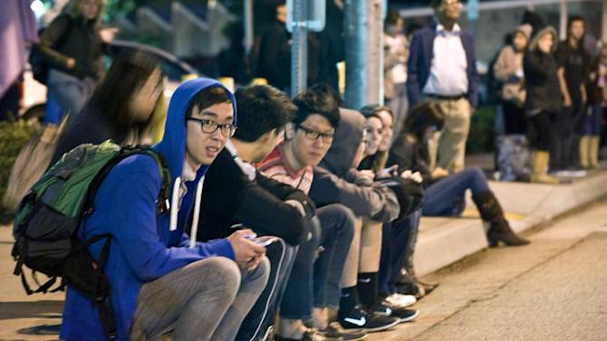 Evacuated students sit on the curb across the street from the Mihaylo College of Business and Economics south of the Cal State Fullerton campus, Wednesday, Dec. 12, 2012, in Fullerton, Calif. Students were placed on lock down as police searched for two suspects in a jewelry store robbery, who were considered armed and dangerous. (AP Photo/The Orange County Register, Bruce Chambers)
