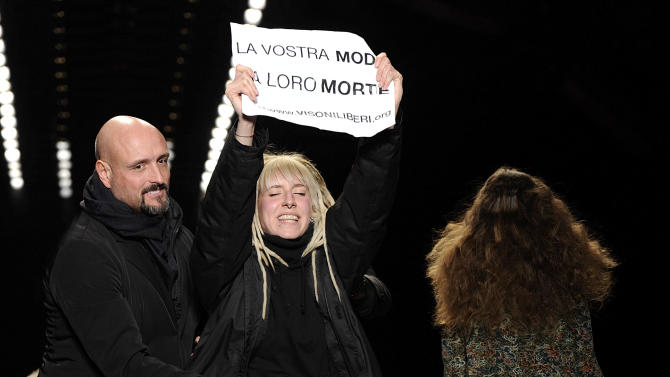 "A security guard stops an animal rights activist walking on the catwalk with a placard reading in Italian ""La vostra moda la loro morte"" (Your fashion their death) during the show of the Just Cavalli women's Fall-Winter 2013-14 collection, part of the Milan Fashion Week, unveiled in Milan, Italy, Thursday, Feb. 21, 2013. (AP Photo/Giuseppe Aresu)"