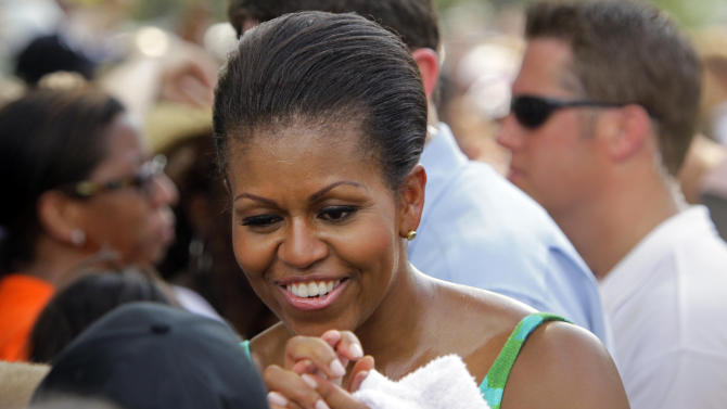 First lady Michelle Obama greets onlookers while she participates during the taping of Extreme Makeover Home Edition in Fayetteville, N.C., Thursday, July 21, 2011. (AP Photo/Gerry Broome)
