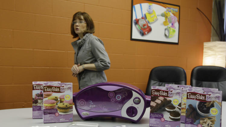 "In this Sept. 8, 2011 photo, Pat Jarret, associate manager of global brand publicity for Hassbro, walks behind the newest version of the company's ""Easy Bake Oven"" in Pawtucket, RI. The toy has been given a top-to-bottom redesign, at the heart of which is a new heating element more like that of a traditional oven.   (AP Photo/Stephan Savoia)"