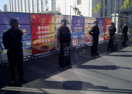 Policemen in riot gear guard a checkpoint on a road near a courthouse where ethnic Uighur academic Ilham Tohti's trial is taking place in Urumqi, Xinjiang Uighur Autonomous Region
