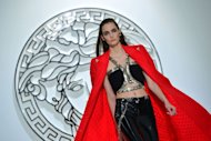 A model displays a creation as part of Versace Fall-Winter 2013-2014 Womenswear collection on February 22, 2013 during the Women's fashion week in Milan. Italian fashion icon Donatella Versace brought her own spin to punk on Friday, unveiling a collection dominated by fierce outfits in shiny black, white, or lipstick red vinyls and deadly accessories