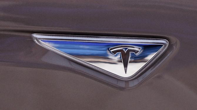 FILE - This April 7, 2015 file photo shows the Tesla logo on the new Tesla Model S 70D during a test drive in Detroit. Electric car maker Tesla Motors reports quarterly financial results on Wednesday, May 6, 2015. (AP Photo/Carlos Osorio, File)