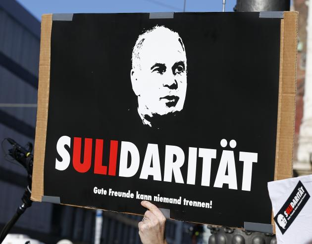 A supporter of Bayern Munich President Uli Hoeness holds up a placard as he awaits the arrival of Hoeness outside the regional court in Munich