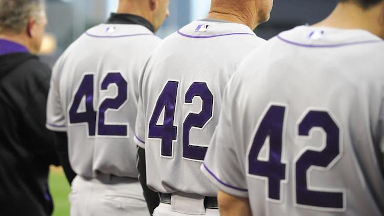 Colorado Rockies' players and coaches wear No. 42 jerseys in honor of Jackie Robinson Day, as they listen to the national anthem before a baseball game against the San Diego Padres, at Petco Park in San Diego, California, on April 15, 2014