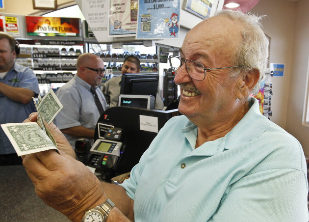 Wes Prinzen, of Fountain Hills, Ariz., smiles as he takes away his modest $4 winnings, at a 4 Sons Food Store where one of the winning tickets in the $579.9 million Powerball jackpot was purchased, No