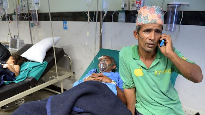 A Nepalese resident talks on the phone as his relative is treated for injuries in a Kathmandu hospital on April 26, 2015