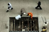 Indian labourers do repair work outside a building in the Nariman Point area of Mumbai on August 13, 2012. India recorded near double-digit expansion over much of the last decade but the economy grew by just 5.3 percent in the January-March quarter, a rate that threatens to stall its transformation since the early 1990s