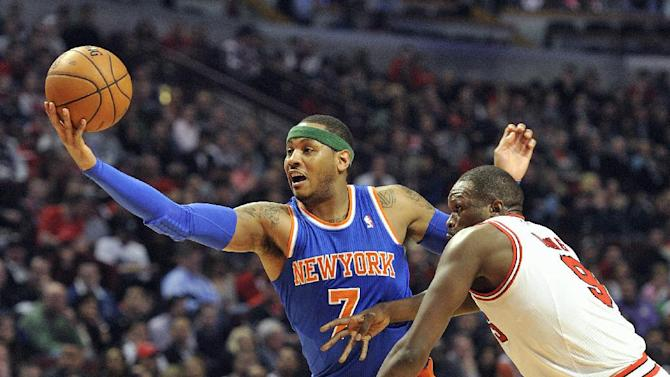 New York Knicks' Carmelo Anthony (7) reaches for the ball as Chicago Bulls' Luol Deng defends during the first half of an NBA basketball game, Thursday, April 11, 2013, in Chicago. (AP Photo/Jim Prisching)