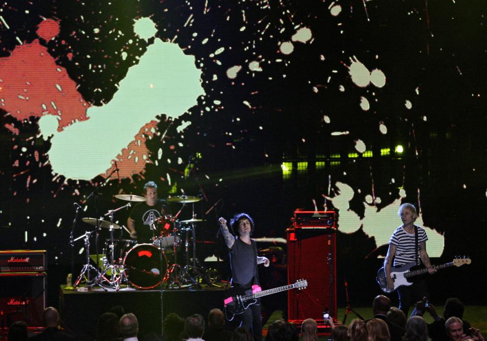 Green Day (from left) Tre Cool, Billy Joe Armstrong and Mike Dirnt, performs to open the 2012 Rock and Roll Hall of Fame induction ceremonies Saturday, April 14, 2012, in Cleveland. Green Day introduce Guns N' Roses for induction into the Rock and Roll Hall of Fame. (AP Photo/Tony Dejak)