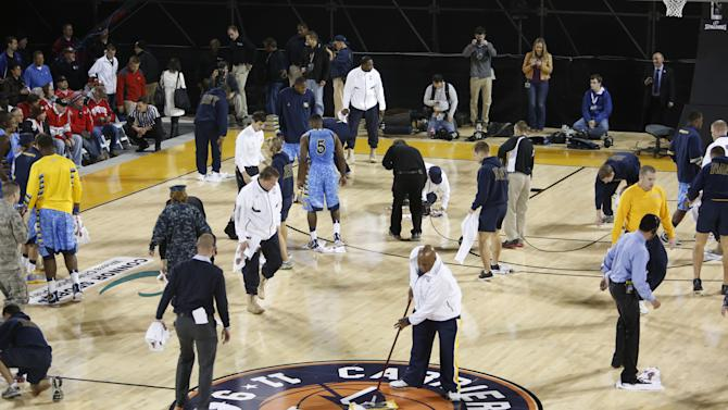 Military personnel and volunteers wipe off condensation in an attempt to dry the damp court before the start of the men's NCAA college basketball game between Ohio Sate and Marquette in the Carrier Classic aboard the USS Yorktown in Mount Pleasant, S.C., Friday, Nov. 9, 2012.  (AP Photo/Mic Smith)