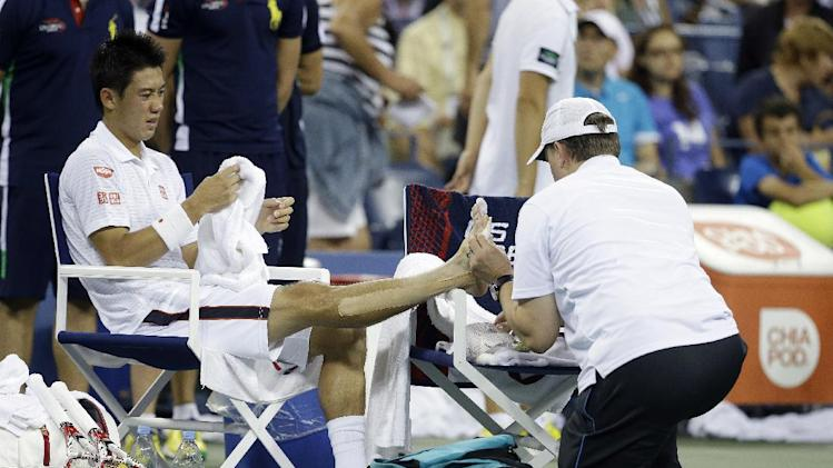 Kei Nishikori, of Japan, is treated by a medical trainer during his match against Milos Raonic, of Canada, in the fourth round of the 2014 U.S. Open tennis tournament Tuesday, Sept. 2, 2014, in New York. (AP Photo/Darron Cummings)