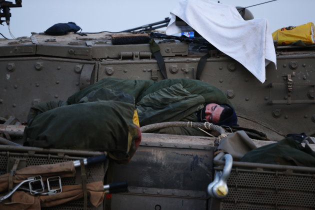 An Israeli soldier sleeps on a tank at a staging area near the Israel Gaza Strip Border, southern Israel, early Tuesday, Nov. 20, 2012.  On Tuesday, grieving Gazans were burying militants and civilian