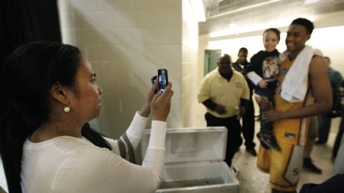 In this photo taken in Chicago on Tuesday, March 13, 2012, Lola Parker, photographs her son Jabari, with a young boy after Parker's Simeon Career Academy won an Illinois state super sectional basketball playoff game. (AP Photo/Charles Rex Arbogast)