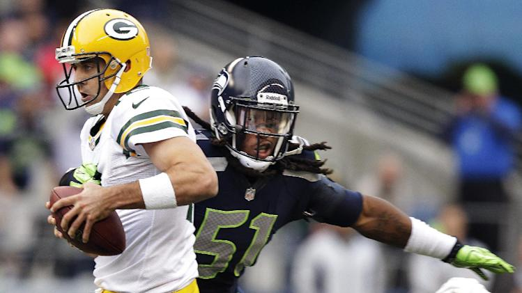 Green Bay Packers quarterback Aaron Rodgers, left, is sacked by Seattle Seahawks defensive end Bruce Irvin (51) in the first half of an NFL football game, Monday, Sept. 24, 2012, in Seattle. (AP Photo/Stephen Brashear)