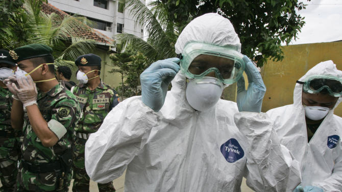 FILE - In this Tuesday, Dec. 16, 2008 file photo, soldiers wear protective gear during a bird flu prevention drill in Jakarta, Indonesia. The second of two bird flu studies once considered too risky to publish was released Thursday, June 21, 2012 ending a saga that pitted concerns about terrorism against fears of a deadly global epidemic. Both papers describe how researchers created virus strains that could potentially be transmitted through the air from person to person. Scientists said the results could help them spot dangerous virus strains in nature. (AP Photo/Irwin Fedriansyah)