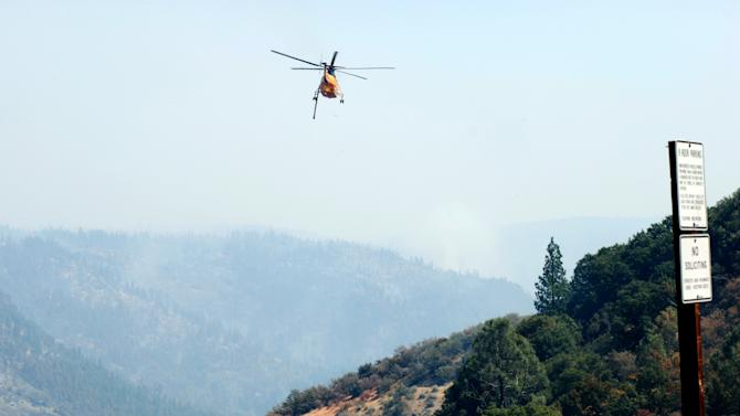 A helicopter drops into Battle Creek Canyon outside Mineral, Calif., on Thursday, Aug. 23, 2012 with a load of fire retardant for the spearhead of the Ponderosa Fire. Fire officials said they were trying to stop the spread of the fire with retardant and water drops to keep it from running up the canyon and through commercial timberland. (AP Photo/Jeff Barnard)