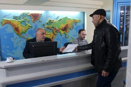 Palestinian travel agent Nabil Shurafa receives a document from a client at his office in Gaza City