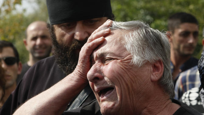 Relatives of inmates demand to see their family members during a protest rally against prison abuse in Tbilisi, Georgia, Thursday, Sept. 20, 2012. Street protests against the brutal abuse of prisoners escalated Thursday in the Georgian capital, fueling anger against the Western-allied government and possibly boosting support for the opposition before a tight parliamentary election. Two days after television stations aired videos of guards beating inmates and raping them with truncheons and brooms, thousands rallied outside the Interior Ministry and the Tbilisi prison where the abuse occurred. The protesters, some carrying brooms, then marched down the capital's main avenue to the presidential palace to demand the ouster of the interior minister. (AP Photo/Shakh Aivazov)
