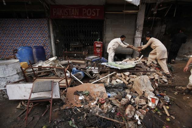 Men collect their belongings from the debris of a damaged building after it was hit by a bomb blast, which happened on Sunday, in Peshawar