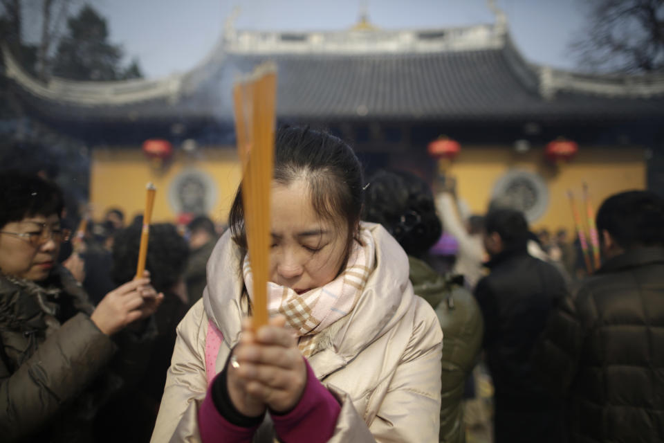 A woman burns joss sticks while praying at Longhua Temple on the first day of the Lunar New Year in Shanghai, China on Sunday, Feb. 10, 2013.  Millions across China are celebrating the arrival of the Lunar New Year, the Year of the Snake, marked with a week-long Spring Festival holiday.   (AP Photo/Eugene Hoshiko)