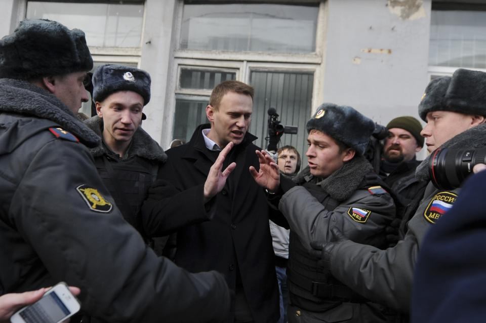 Opposition leader Alexei Navalny, center, is detained by police  in Moscow, Saturday Oct. 27, 2012. Opposition leaders and activists held a one-man picket against torture in Russia. (AP Photo/Sergey Ponomarev)