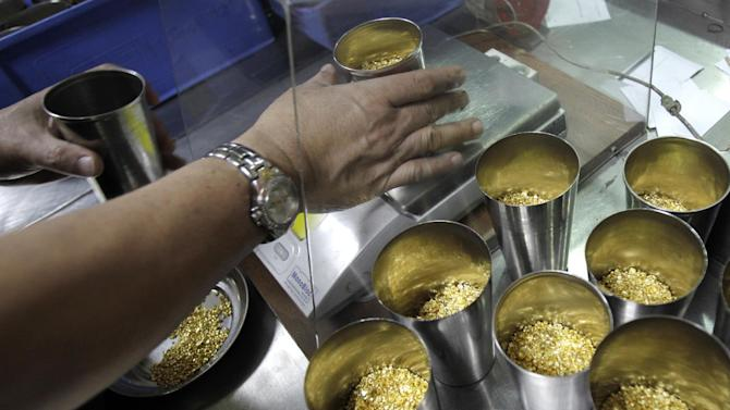 In this Tuesday Oct. 9, 2012 photo, technician prepares 1 Kg containers of gold grains for melting into 995.0 purity gold bars at the Emirates Gold refinery in Dubai, United Arab Emirates. Dubai now has about a 29 percent market share of global gold trade with nearly 1,200 tons -- worth about $41 billion -- changing hands annually in the city's gold markets, according to the gold industry website bullionstreet.com. At the Dubai Gold and Commodities Exchange, traders and speculators buy and sell the metal on the futures market. (AP Photo/Kamran Jebreili)