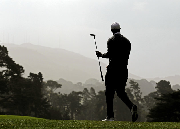 Tiger Woods walks off the 17th green during the first round of the U.S. Open Championship golf tournament Thursday, June 14, 2012, at The Olympic Club in San Francisco. (AP Photo/Charlie Riedel)