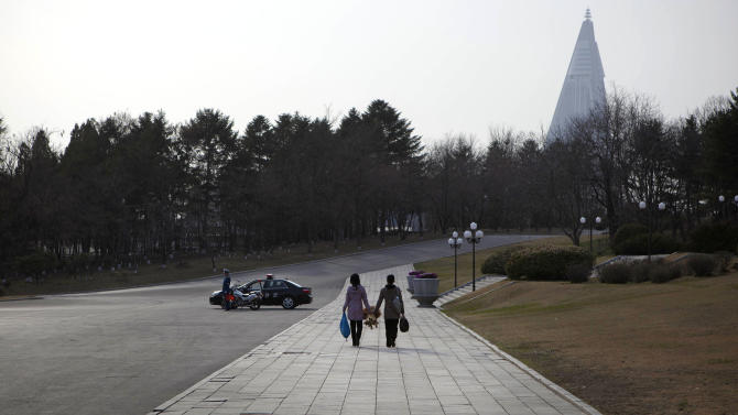 North Korean women carry a bundle of brooms after the cleaning of the area around bronze statues of the late leaders Kim Il Sung and Kim Jong Il in Pyongyang on Monday, April 15, 2013. Oblivious to international tensions over a possible North Korean missile launch, Pyongyang residents spilled into the streets Monday to celebrate a major national holiday, the birthday of their first leader, Kim Il Sung. (AP Photo/David Guttenfelder)