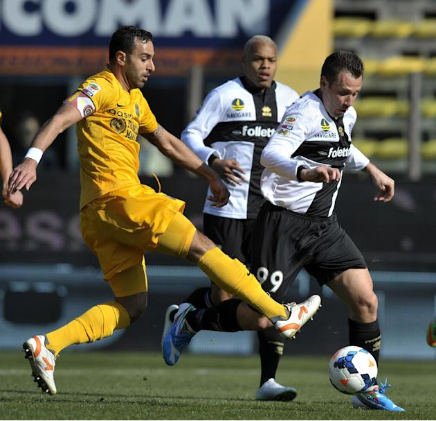 Parma's Antonio Cassano, right, vies for the ball with Verona's Domenico Maietta, during their Serie A soccer match at Parma's Tardini stadium, Italy, Sunday, March 9, 2014