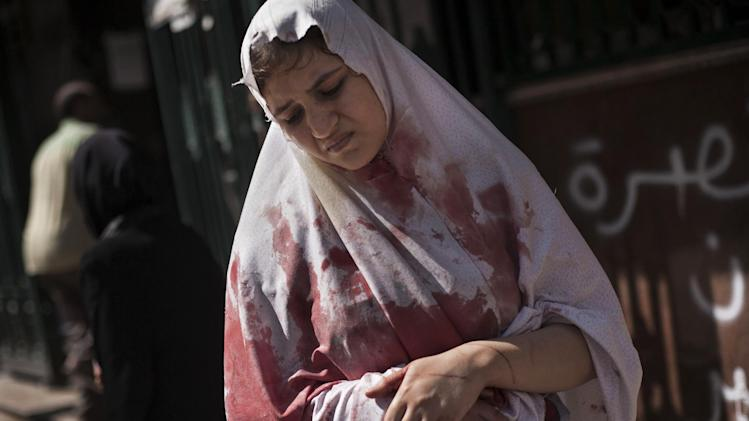 FILE - In this Sept. 20, 2012 file photo, A wounded woman still in shock leaves Dar El Shifa hospital in Aleppo, Syria. More than 100,000 people have been killed since the start of Syria's conflict over two years ago, an activist group said Wednesday. (AP Photo/Manu Brabo, File)