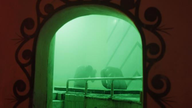 """Men relax at a steam room full before diving into cold water at a traditional steam bath """"hammam"""" in Cairo"""
