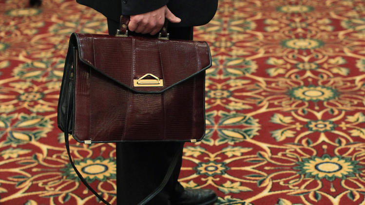 A man holds his briefcase while waiting in line during a job fair in Melville, New York