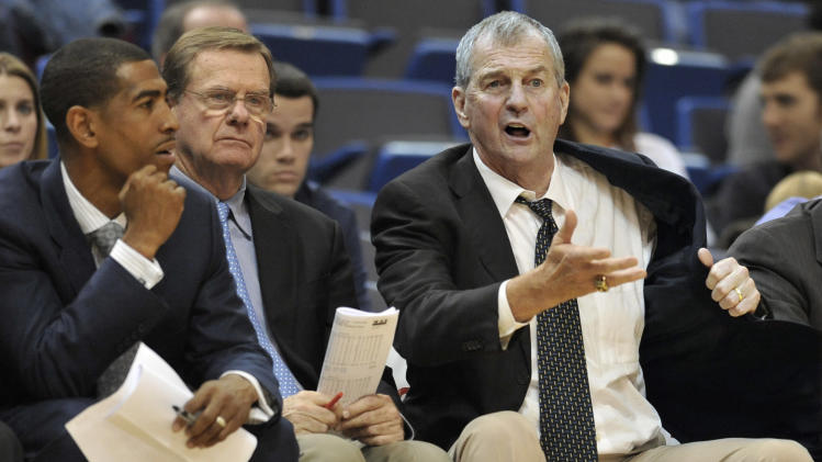 FILE - In this Nov. 20, 2011, file photo, Connecticut head coach Jim Calhoun, right, gestures as assistant coach Kevin Ollie, left, and associate head coach George Blaney, center, look on during the second half of an NCAA college basketball game against Coppin State in Hartford, Conn. Calhoun is retiring and plans to announce his decision on Thursday, a person familiar with the decision told The Associated Press. Ollie was expected to replace Calhoun, the person said. (AP Photo/Jessica Hill, File)