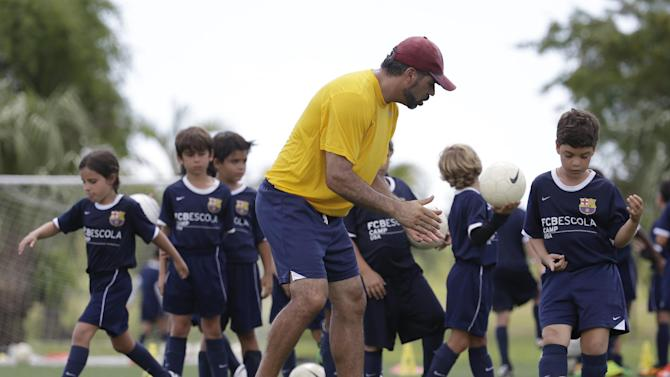 In this Thursday, Aug. 1, 2014 photo, Lee Santamaria, front, of Cooper City, Fla., works with children during a soccer camp held by FC Barcelona in Miami. European clubs like Barcelona, Liverpool and Arsenal have long sent coaches to work at U.S. summer camps, but now some are opening year-round U.S. academies aimed at finding new talent but also to expand their fan bases. This is part of a number of initiatives of major teams to grow their brands in the U.S